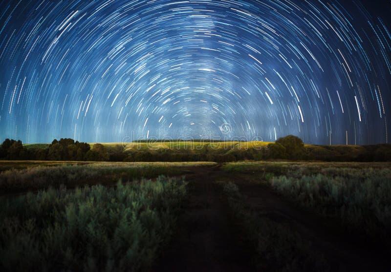 Schöner nächtlicher Himmel, Milchstraße, Sternspuren und die Bäume stockfoto