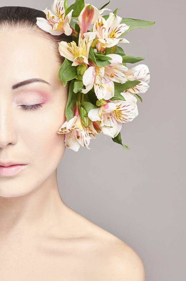Schöner nackter attraktiver Brunette mit Blumen auf seinem Kopf Arbeiten Sie schönes Make-up, saubere Haut, Gesichtspflege um Por stockbilder
