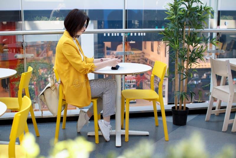 Schöner netter Brunette in einer gelben Jacke Junge Geschäftsfrau in einem Café unter Verwendung eines digitalen Tablettenlaufens lizenzfreies stockfoto