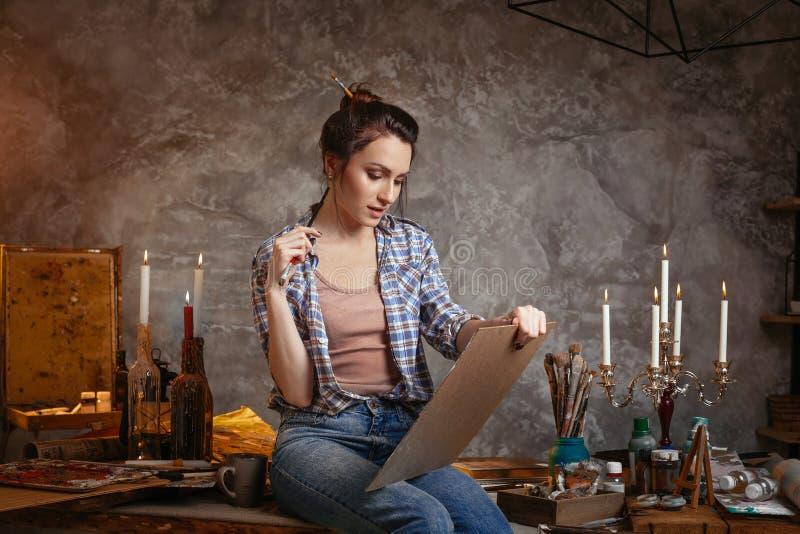 Schöner netter professioneller junger weiblicher Künstler, der an neuem kreativem Projekt, Zeichnung, Gefühl angespornt arbeitet lizenzfreie stockbilder