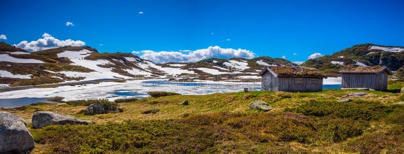 Schöner norwegischer schmelzender See mit traditionellen hölzernen Kabinen in Norwegen stockfotos