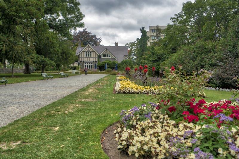 Schöner Park mit Blumen in voller Blüte und grünem Gras lizenzfreie stockfotografie