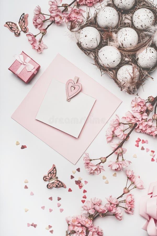 Schöner Pastellrosa Ostern-Grußkartenspott oben mit Blütendekoration, Herzen, Eier im Kartonkasten auf weißem Schreibtisch stockfotografie