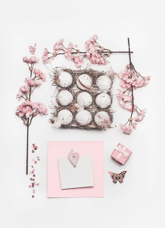 Schöner Pastellrosa Ostern-Plan mit Blütendekoration, Herzen, Eiern im Kartonkasten und Grußkartenspott oben lizenzfreies stockbild