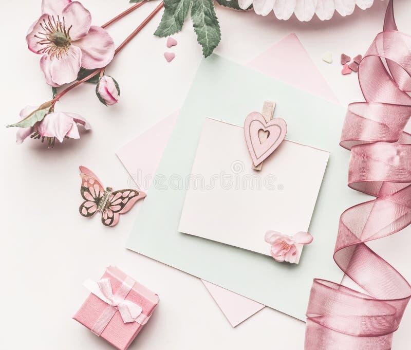 Schöner Pastellrosaplan mit Blumendekoration, Band, Herzen und Kartenspott oben auf weißem Schreibtischhintergrund, Draufsicht, f lizenzfreies stockbild