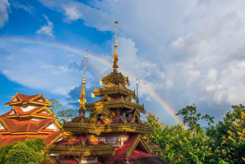 Schöner Regenbogen über dem alten hölzernen Tempel Shan-thailändischer Buddhismustempel Tropische Bäume sind in den Blütenhinterg lizenzfreies stockfoto
