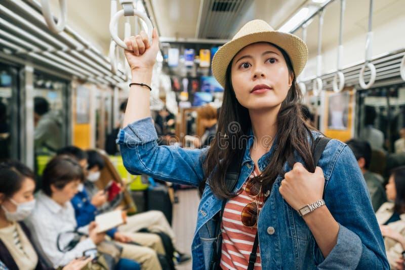 Schöner Reisender des jungen Mädchens, der die Metro zurück geht zum Hotel am nigth nimmt elegante asiatische touristische halten stockbild