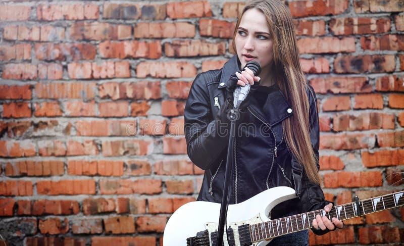Schöner Rocker des jungen Mädchens mit E-Gitarre Ein Felsen musicia stockfoto