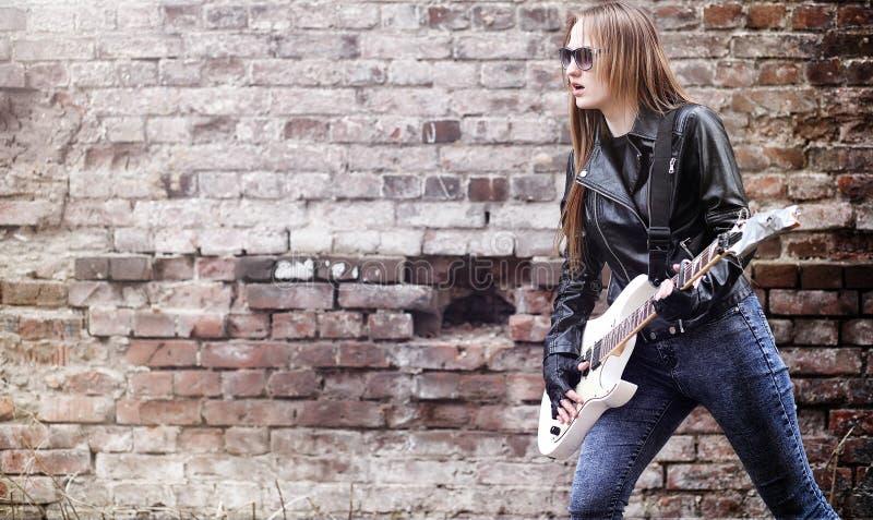 Schöner Rocker des jungen Mädchens mit E-Gitarre Ein Felsen musicia lizenzfreie stockfotografie