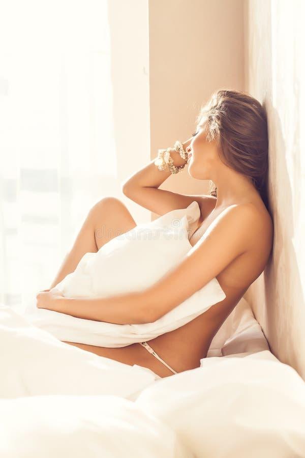 Schöner romantischer Frau/Mädchen Brunette, der zu Hause auf dem Bett in ihrem Raum liegt stockfotos