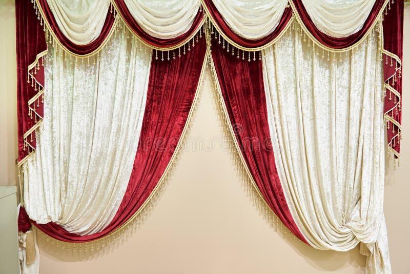 Schöner roter weißer Samtvorhang auf beige Wand stockfoto