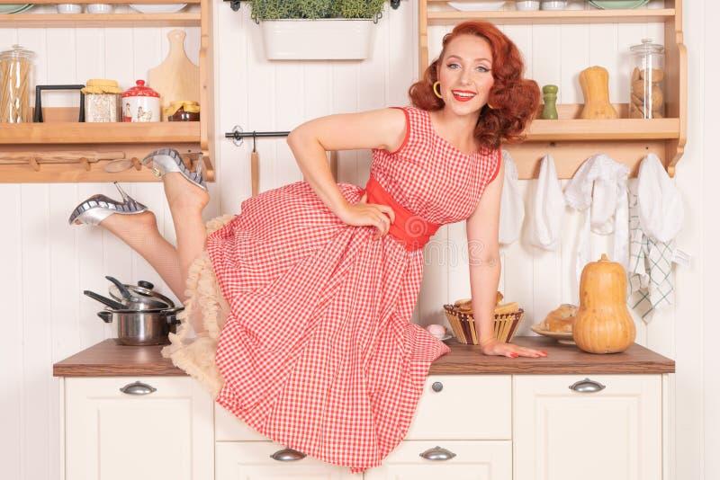 Schöner rothaariger Pinup, der glücklich Mädchen aufwirft in einem Retro- roten Kleid in der Küche allein lächelt lizenzfreie stockfotos