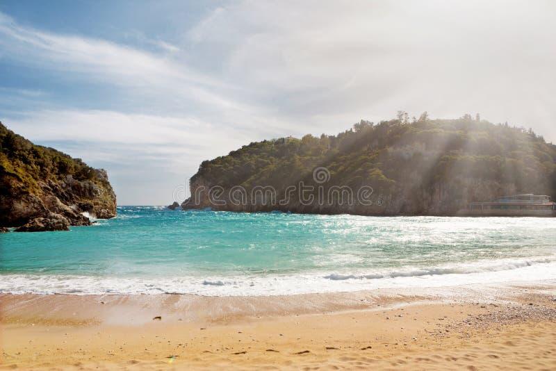Schöner sandiger Strand mit Sonnenstrahl bei Paleokastritsa in Korfu, G lizenzfreies stockfoto