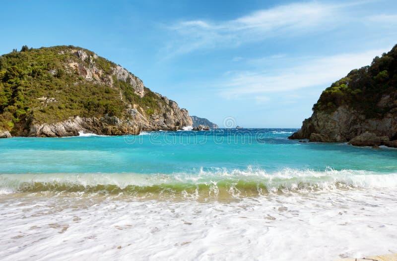 Schöner sandiger Strand und Wellen in einer Bucht bei Paleokastritsa lizenzfreies stockfoto