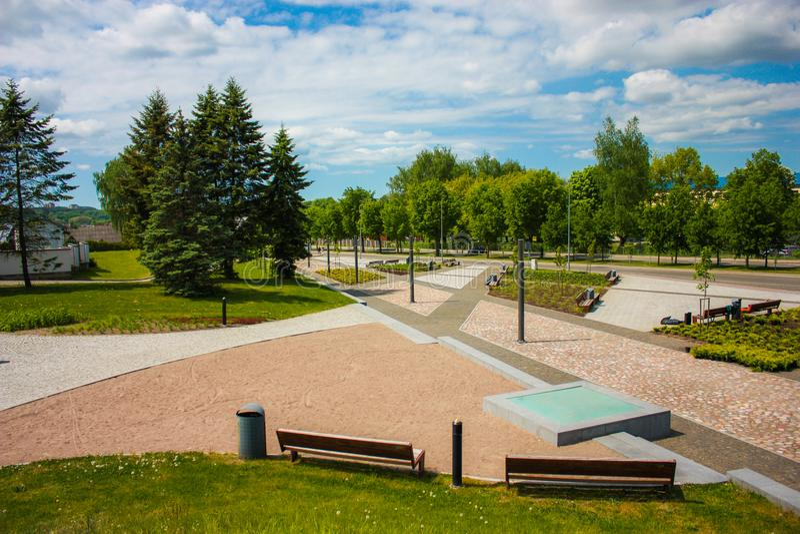Schöner sauberer Park mit Weihnachtsbäumen und Blumensträußen von Blumen lizenzfreies stockbild