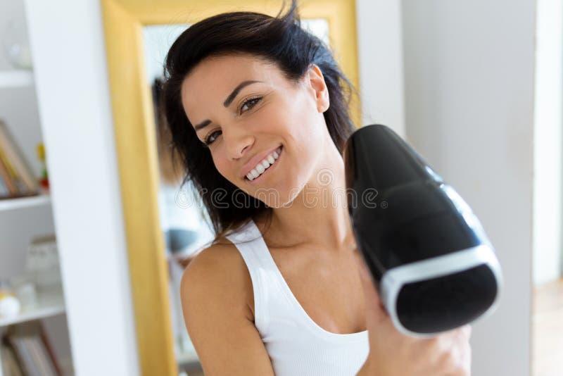 Schöner Schlag der jungen Frau, der ihr Haar nahe dem Spiegel im Badezimmer trocknet stockfotografie