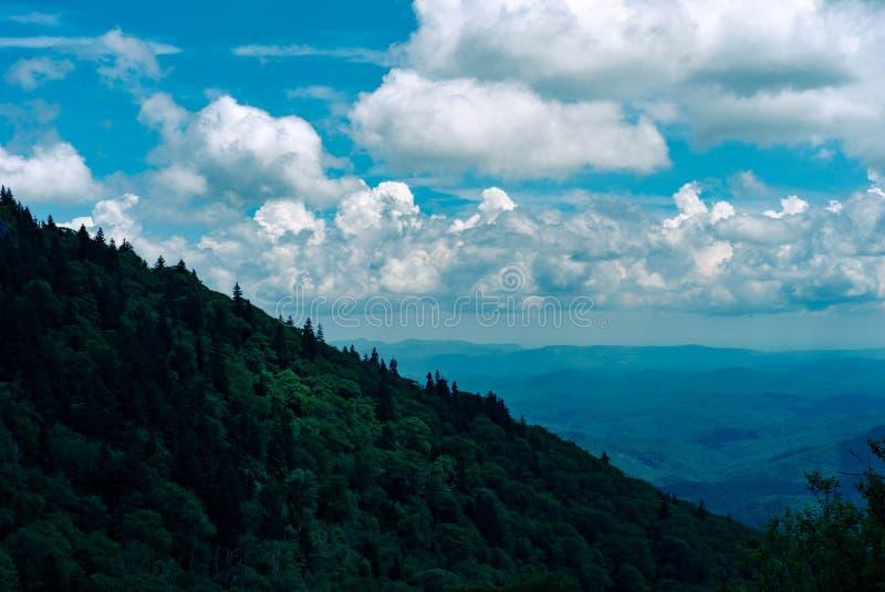 Schöner Schuss eines grünen Hügels mit dem Ozean und der überraschenden Wolken im Himmel lizenzfreie stockfotos
