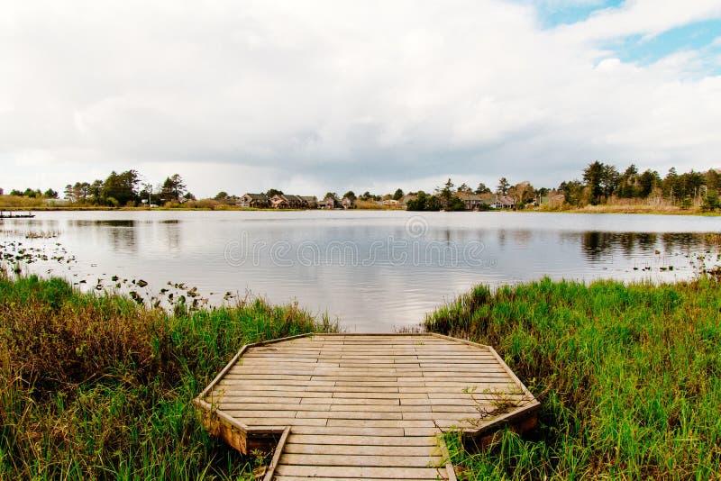 Schöner Schuss eines hölzernen Docks an einem See in einem Wald stockfotografie