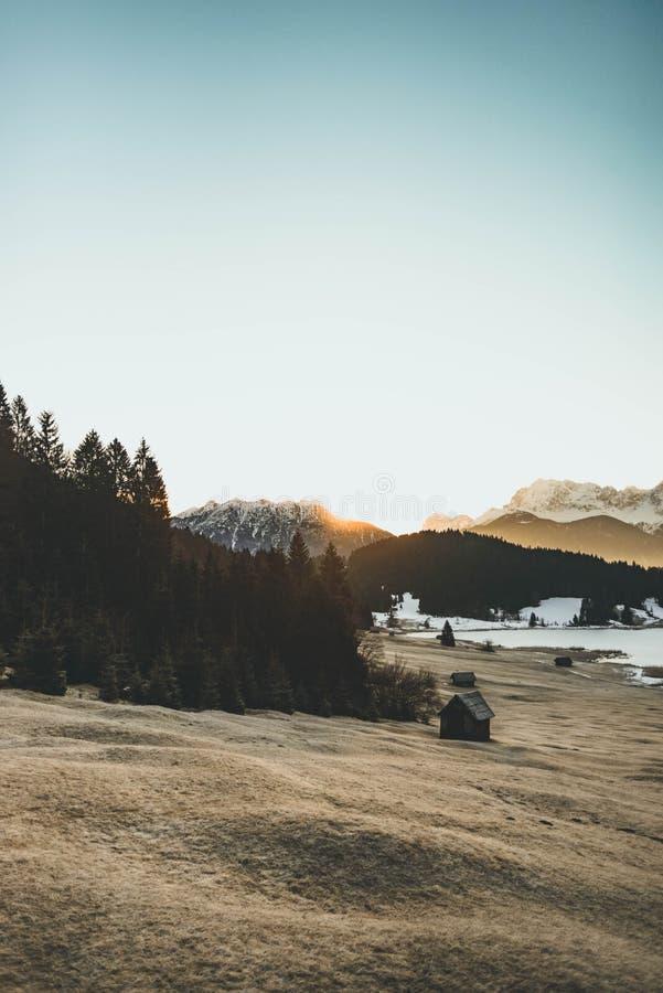 Schöner Schuss eines Hügels mit Bäumen und einer hölzernen Hütte und der Berge im Hintergrund stockfotografie