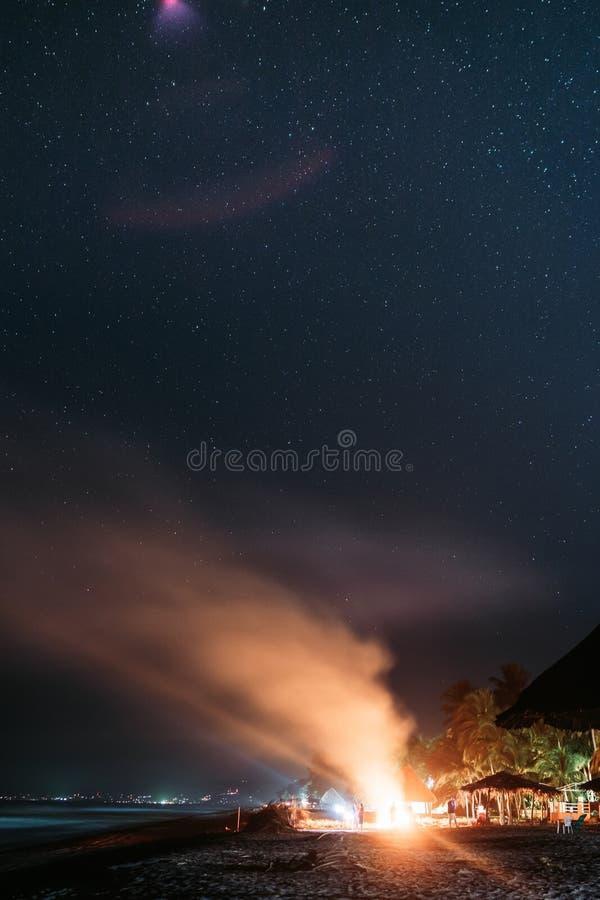 Schöner Schuss eines Lagerfeuers mit dem Rauche, der steigen und einem erstaunlichen sternenklaren nächtlichen Himmel stockbild