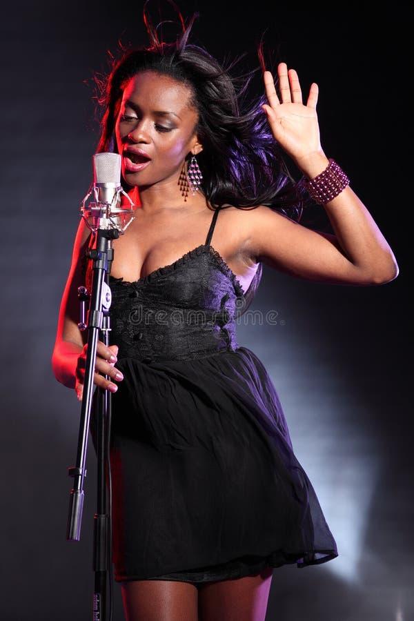 Schöner schwarzer Sänger auf Stufe mit Mikrofon stockfotos