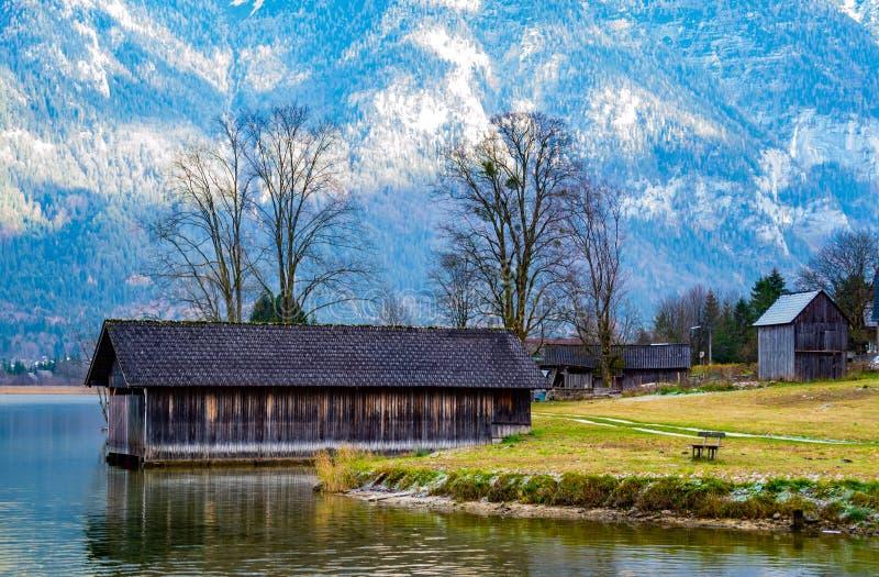 Schöner See in den Bergen, einsame Bank, im Hintergrund ein Holzhaus stockfotografie