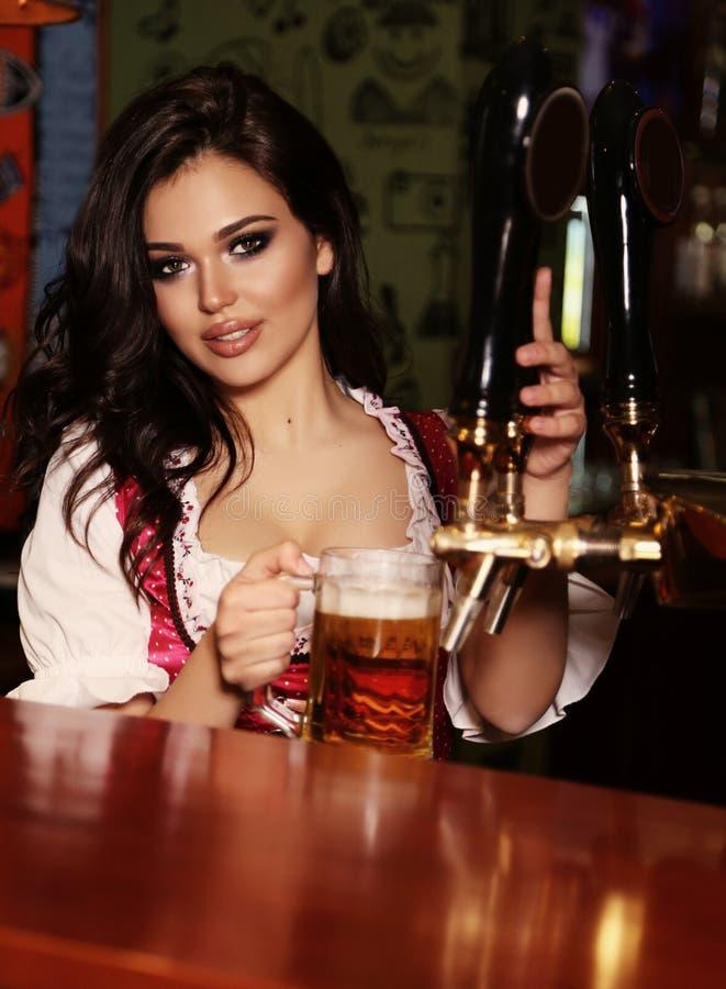 Schöner sexy Frauenbarmixer, der im Barzähler mit Bier aufwirft stockfoto