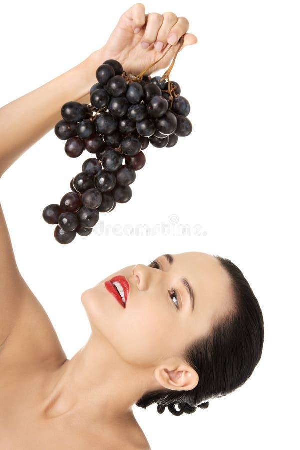 Schöner sinnlicher Brunette, der Trauben isst lizenzfreie stockfotos