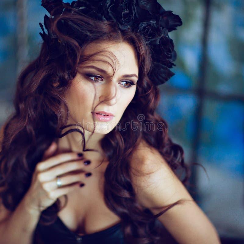 Schöner sinnlicher Brunette mit einem Kranz des Schwarzen blüht sittin stockfoto