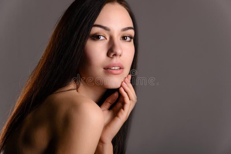 Schöner sinnlicher Brunette was die Hand anbetrifft seines Gesichtes lizenzfreies stockbild