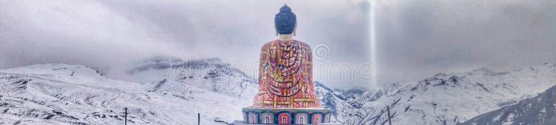 Schöner sitzender Buddha und schönes Natur- und Schneeweiß stockbild