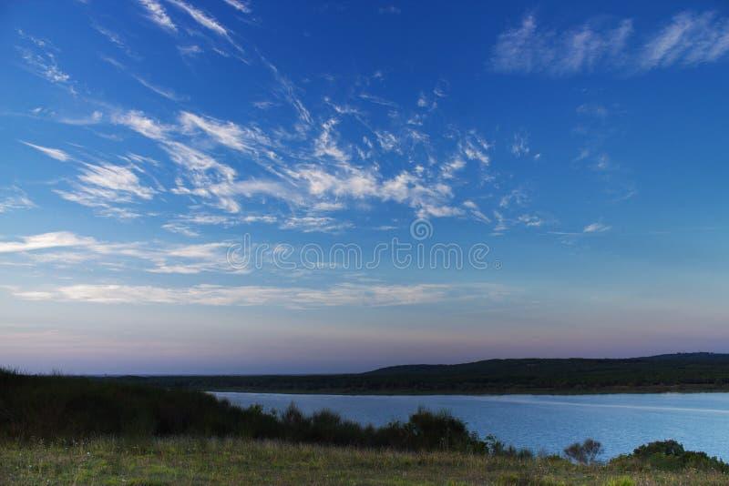 Schöner Sommersonnenuntergang über ein See und Waldwolken auf blauem Himmel stockfotografie