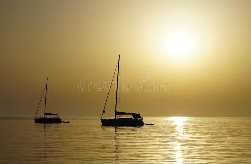 Schöner Sommersonnenunterganghintergrund im beige Farbton mit Schattenbild von zwei Yachten auf der Seehorizontlinie stockbild