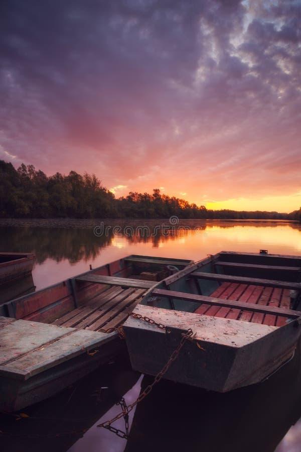 Schöner Sonnenaufgang über Fluss mit verankerten Fischerbooten lizenzfreie stockfotografie