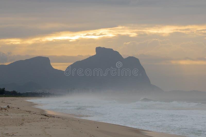 Schöner Sonnenaufgang auf dem Strand von Barra da Tijuca mit dem Stein von GÃ-¡ vea im Hintergrund stockfoto