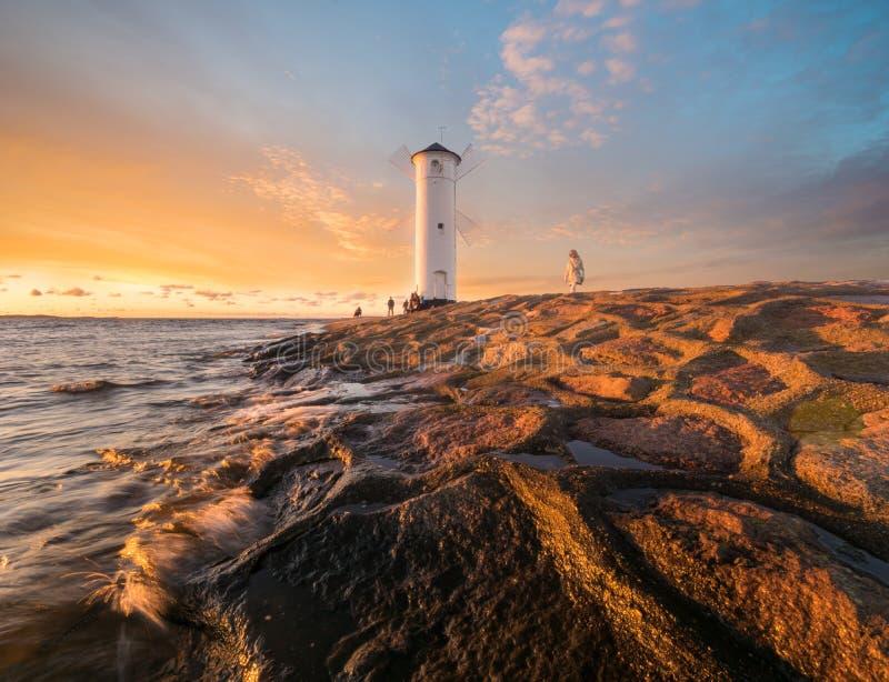 Schöner Sonnenuntergang über einem Windmühle-förmigen Leuchtturm, Swinoujscie, stockbild
