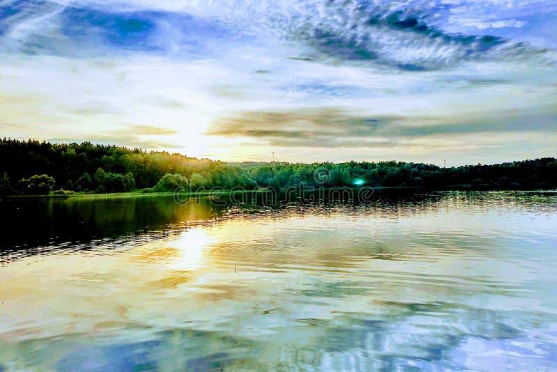 Schöner Sonnenuntergang auf dem See oder dem Fluss Feld des gr?nen Grases gegen einen blauen Himmel mit wispy wei?en Wolken stockfoto