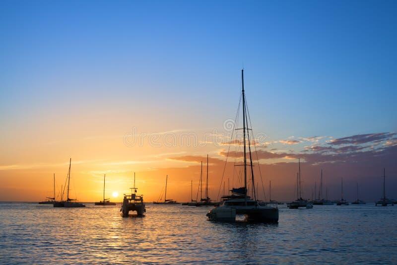 Schöner Sonnenuntergang auf dem Seestrand, -booten, -schiffen und -yachten auf Wasserhintergrund lizenzfreies stockbild