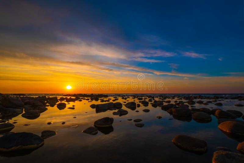 Schöner Sonnenuntergang an der Seeseite mit Steinen lizenzfreie stockfotos