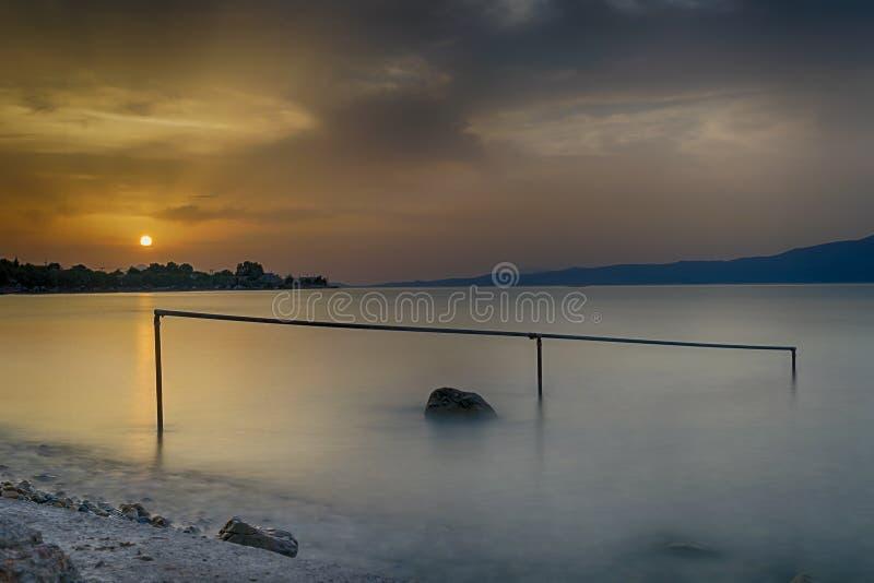 Schöner Sonnenuntergang an einem Strand mit einem Felsen und an einer Bar als Vordergrund bei Oropos in Griechenland Lange Berühr stockbild