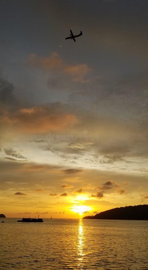 Schöner Sonnenuntergang, Flugzeug herüber, Fischerboote, warmer Sonnenuntergang, bunte Wolken, goldenes Meer lizenzfreie stockfotografie