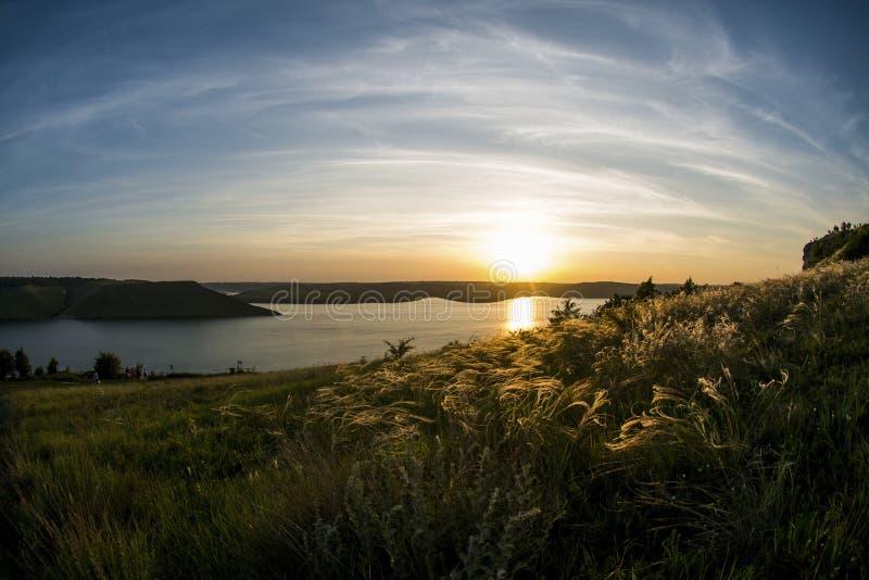 Schöner Sonnenuntergang mit enormem Fluss und Hügeln stockfotografie