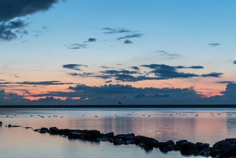 Schöner Sonnenuntergang mit Felsen im Vordergrund und Vögeln im Ba lizenzfreie stockfotografie