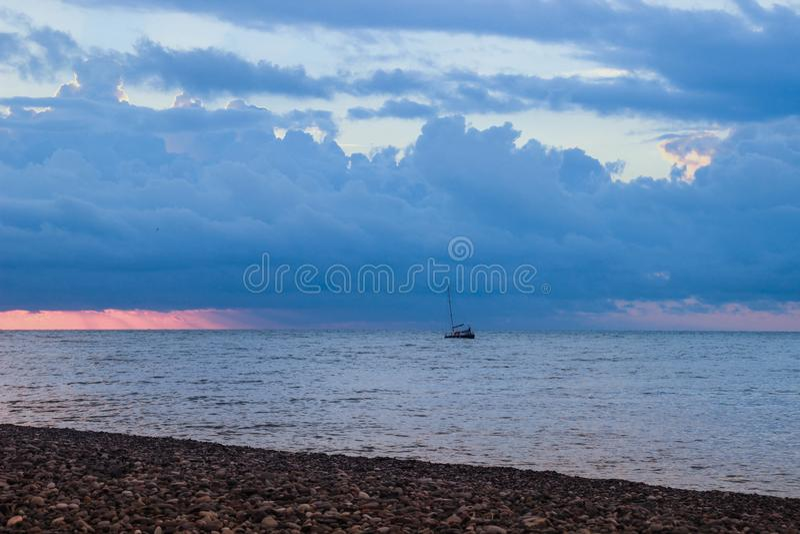 Schöner Sonnenuntergang mit hellen Wolken über dem Meer Die Küste wird mit Kieseln und einem Segelschiff punktiert lizenzfreie stockbilder