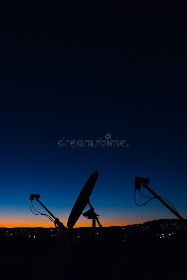 Schöner Sonnenuntergang mit Satellitenschüssel-Schattenbild stockbild