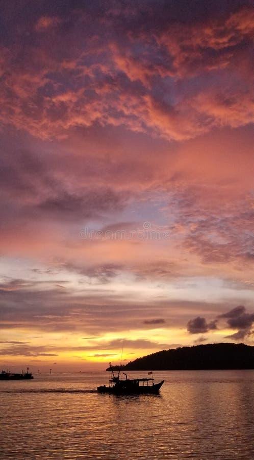 Schöner Sonnenuntergang, schnelle Fischerboote, warmer Sonnenuntergang, bunte Wolken stockfotos