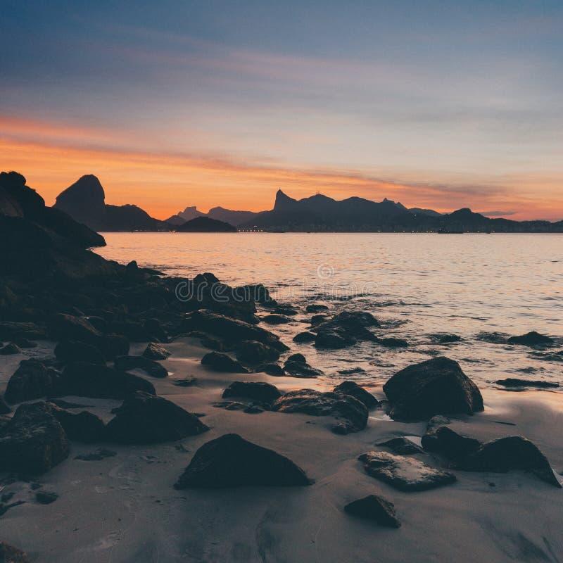 Schöner Sonnenuntergang am steinernen Strand von Niteroi, Brasilien stockfotografie