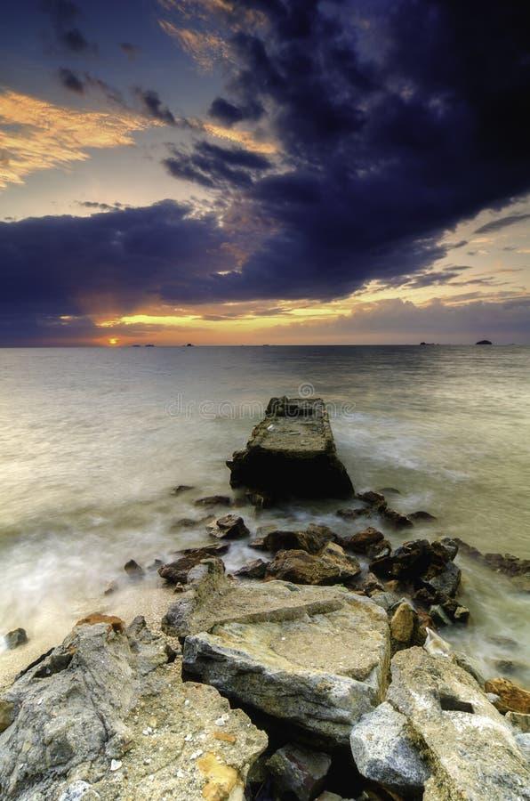Schöner Sonnenuntergang am Strand mit drastischen weichen und dunklen Wolken lizenzfreie stockfotos