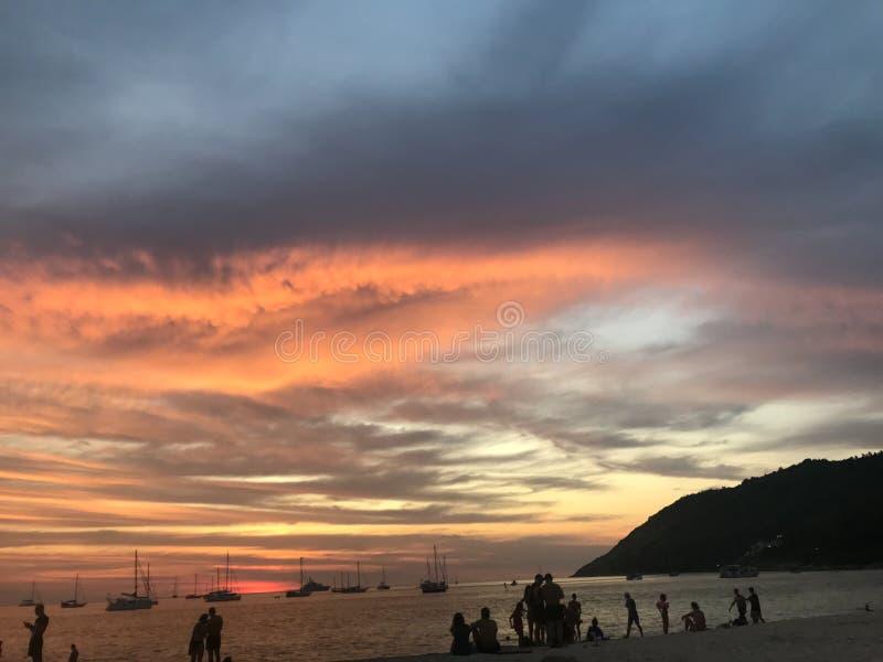Sch?ner Sonnenunterganghimmel und -leute auf dem Strand lizenzfreie stockbilder