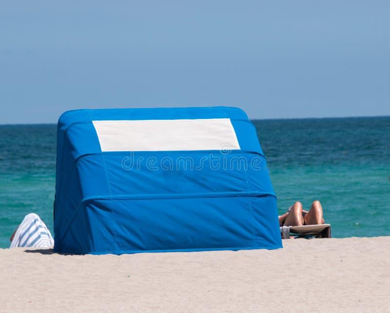 Schöner sonniger Strand mit Sunbather und Cabana mit blauem Ozean stockfoto